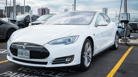 Burlington, Canada - February 29, 2016: A white colored Tesla Model S electric car being charged at a parking lot in Burlington, Ontario.