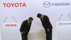 Toyota Motor Corp. President Akio Toyoda, left, and Mazda Motor Corp. President Masamichi Kogai, right, bow to each other prior to a press conference in Tokyo Friday, Aug. 4, 2017.  Japanese automakers Toyota Motor Corp. and Mazda Motor Corp. said Friday they plan to spend $1.6 billion to set up a joint-venture auto manufacturing plant in the U.S. — a move that will create up to 4,000 jobs. (AP Photo/Eugene Hoshiko)