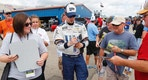 Brad Keselowski signs autographs after practice the NASCAR Cup Series auto race in Brooklyn, Mich., Saturday, Aug. 12, 2017. (AP Photo/Paul Sancya)