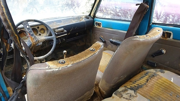 An interior view of a Peugeot 104, which was recovered this week 38 years after it was stolen, stored in a garage in Chalons-en-Champagne, eastern France, Friday, Sept. 1, 2017. A blue Peugeot 104 stolen in the heart of France's Champagne country in 1979 is being reunited with its owner - 38 years later - after French police pulled it, in surprisingly good shape but teeming with crayfish, from a murky swamp. (AP Photo/Chris den Hond)