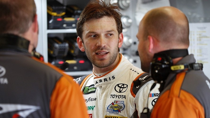 Daniel Suarez, of Mexico, talks with crew members after practice for the NASCAR Cup Series auto race in Brooklyn, Mich., Saturday, Aug. 12, 2017. (AP Photo/Paul Sancya)