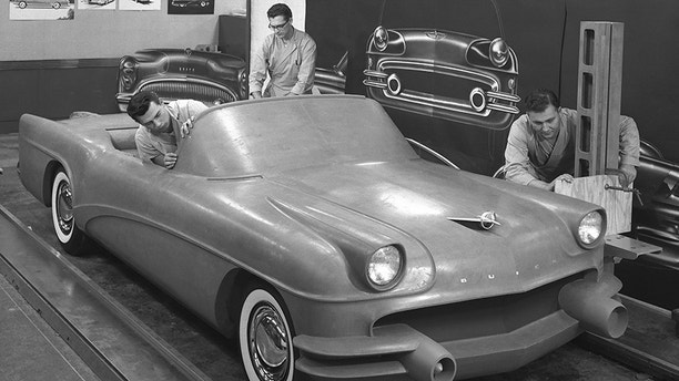 This 1954 photo Courtesy of General Motors shows Buick Design Studio creative clay sculptors as they mold the clay on a model GM automobile. (Courtesy of General Motors via AP)