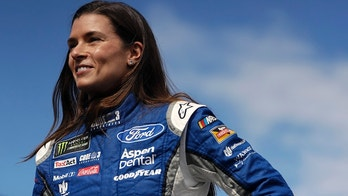 FILE - In this July 29, 2017, file photo, Danica Patrick stands near the garage area after practice for a NASCAR Cup series auto race in Long Pond, Pa. Danica Patrick will honor NASCAR Hall of Fame inductee Robert Yates at NASCAR's throwback weekend at Darlington Raceway for the Southern 500. Patrick's No. 10 Ford will feature the paint scheme used by Yates' driver Dale Jarrett from 1996 through 2000. Yates said seeing the old, red, white and blue paint scheme run by Jarrett's No. 88 will bring back great memories. (AP Photo/Matt Slocum, File)