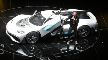 Formula One driver Lewis Hamilton leaves the Mercedes-AMG Project One hyper car after driving it onto the stage during the first media day of the International Frankfurt Motor Show IAA in Frankfurt, Germany, Tuesday, Sept. 12, 2017, which runs through Sept. 24, 2017. (AP Photo/Michael Probst)