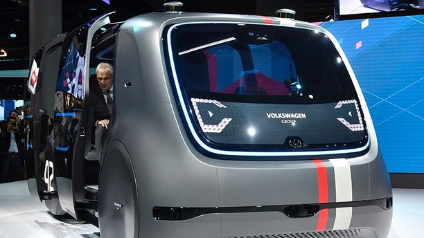 Volkswagen CEO Matthias Mueller arrives a self-driving electric vehicle for an event of German carmaker Volkswagen on the eve of the opening of the International Frankfurt Motor Show IAA in Frankfurt, Germany, Monday, Sept. 11, 2017, which runs through Sept. 24, 2017. (AP Photo/Martin Meissner)