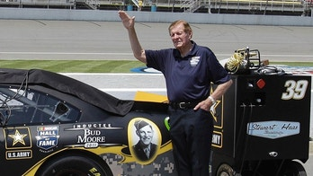 FILE - In this June 18, 2011, file photo, NASCAR Hall of Famer Bud Moore stands next to Ryan Newman's car before qualifying laps for a NASCAR Sprint Cup Series auto race at Michigan International Speedway in Brooklyn, Mich. NASCAR Hall of Famer Bud Moore, a World War II veteran awarded five Purple Hearts and two Bronze Stars, has died. He was 92. NASCAR announced the death of Moore, born Walter Moore Jr., on Tuesday, Nov. 28, 2017. No details were given, but Moore lived in Spartanburg, South Carolina.(AP Photo/Carlos Osorio)