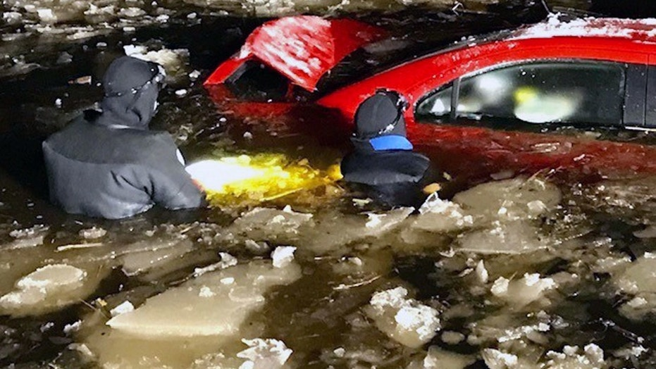 Driver rescued from car quickly sinking into icy pond
