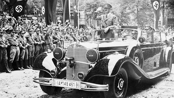 (Original Caption) Storm Troopers, with arms linked, hold back the crowds, as the leader of the Reich, Adolf Hitler, returns to Berlin after the triumph of his Armies in France. He returned on July 6th, 1940, after having visited conquered Paris. The street is strewn with flowers. Hitler stands upright in his official car and returns the salutes of his greeters.