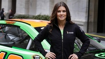 FILE - In this April 1, 2015, file photo, face car driver Danica Patrick poses with her car in front of the New York Stock Exchange before the GoDaddy IPO. GoDaddy tells The Associated Press it is partnering with Patrick as she closes her career with the Daytona 500 and the Indianapolis 500. (AP Photo/Richard Drew, File)