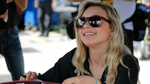 Natalie Decker, pole sitter for the ARCA auto race at Daytona International Speedway, signs autographs, Saturday, Feb. 10, 2018, in Daytona Beach, Fla. (AP Photo/Terry Renna)