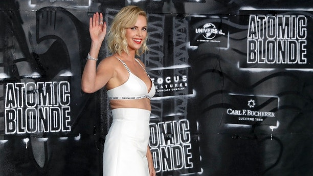 FILE - In this July 17, 2017, file photo, actress Charlize Theron waves as she arrives for the world premiere of the movie 'Atomic Blonde' in Berlin, Germany. Academy Award winner Charlize Theron has been named honorary starter for the 60th running of the Daytona 500. The 42-year-old actress will wave the green flag for the season-opening race Sunday in NASCAR's Monster Energy Cup Series. (AP Photo/Michael Sohn, File)