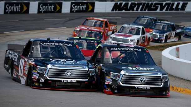 MARTINSVILLE, VA - APRIL 02:  Ben Rhodes, driver of the #41 Alpha Energy Solutions Toyota, and Kyle Busch, driver of the #18 Toyota Toyota, leads a pack of cars during the NASCAR Camping World Truck Series Alpha Energy Solutions 250 at Martinsville Speedway on April 2, 2016 in Martinsville, Virginia.  (Photo by Brian Lawdermilk/Getty Images)