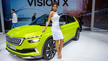In this March 6, 2018 a hostess poses next to a Skoda Vision X, during a press day at the 88th Geneva International Motor Show in Geneva, Switzerland. Some automakers want visitors to focus their minds more on the models _ the cars, not the women. In the wake of the #MeToo movement and growing concerns about sexual harassment, some leading car business executives have been taking a new look at its traditional use of often scantily-clad women on display stands, as attractive, smiling accessories to the vehicles at auto shows. (Martial Trezzini/Keystone via AP)