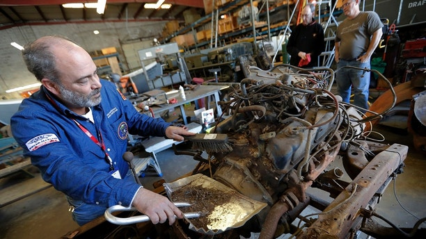 Bill Hall, a volunteer restoration specialist for the National WWII Museum, removes debris off the dilapidated engine of 1940's era fire truck, in their warehouse in New Orleans, Wednesday, March 7, 2018. The National World War II Museum is taking apart the recently acquired fire engine, made for the military home front in 1943, and expects to have it rolling and ready for display in two or three years. (AP Photo/Gerald Herbert)