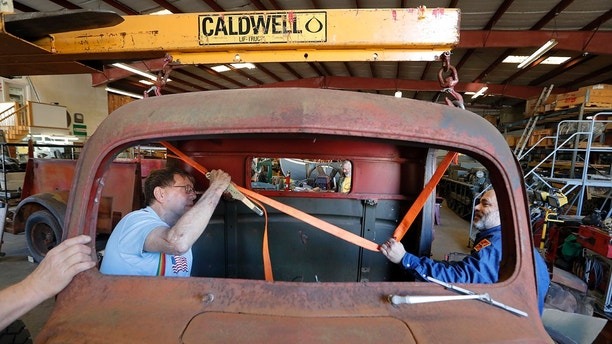 Bill Hall, right, and Eldon Huner, Jr. volunteer restoration specialists for the National WWII Museum, prepare to hoist the cab off of a 1940's era fire truck, in their warehouse in New Orleans, Wednesday, March 7, 2018. The National World War II Museum is taking apart the recently acquired fire engine, made for the military home front in 1943, and expects to have it rolling and ready for display in two or three years. (AP Photo/Gerald Herbert)