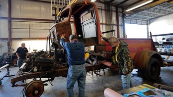 Restoration specialists for the National WWII Museum lift off the cab of a 1940's era fire truck, in their warehouse in New Orleans, Wednesday, March 7, 2018. The National World War II Museum is taking apart the recently acquired fire engine, made for the military home front in 1943, and expects to have it rolling and ready for display in two or three years. (AP Photo/Gerald Herbert)