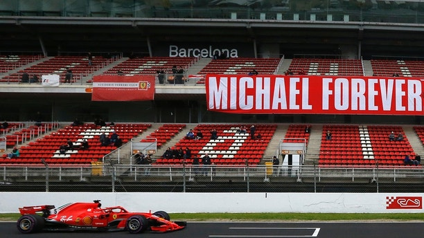 FILE - In this Thursday, March 8, 2018 file photo, Ferrari driver Sebastian Vettel of Germany drives by a tribute-banner in honour of former German driver Michael Schumacher during a Formula One pre-season testing session in Montmelo, outside Barcelona, Spain. As Formula One drivers prepare to contest the season-opening Australian Grand Prix on March 25, 2018 far away on another continent F1's most successful driver continues a very different fight. Respect remains huge for Michael Schumacher, the seven-time F1 champion whose feats will never be forgotten and records maybe never beaten.  (AP Photo/Manu Fernandez, File)