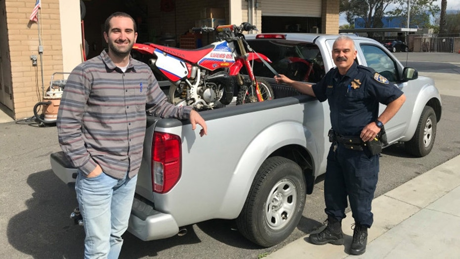 Kamron Golbaf retrieving his motorcycle from CHP officer Ralph Villegas at the Temecula station.