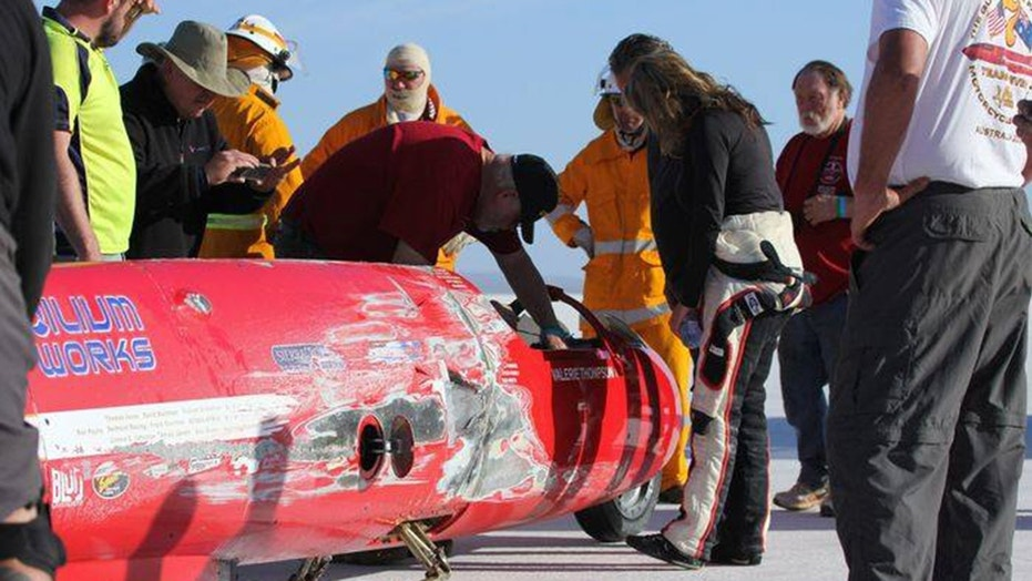 Valerie Thompson checks out her streamlined motorcycle after it wrecked on Australia's Lake Gairdner