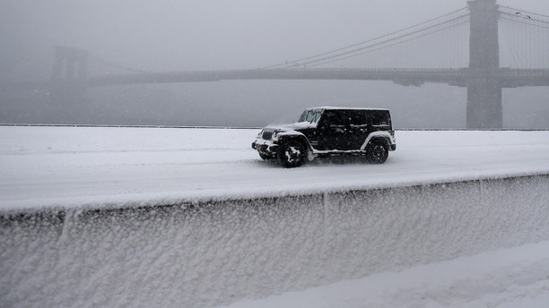 A jeep makes its way north though heavy snow on the FDR Drive with the Brooklyn Bridge in background during a snowstorm in the Manhattan borough of New York, January 23, 2016.     REUTERS/Carlo Allegri - GF20000104624