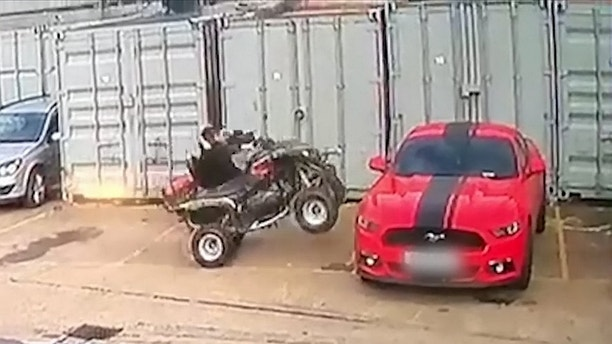 """This was the shocking moment a man drove a quad bike into his brand new sports car - worth nearly £50,000.  See SWNS story SWQUAD.  Andy Quay, 25, was trying to park the quad bike, which belongs to a pal, beside his red Ford Mustang GT500, which he bought less than a year ago.  But as he took his foot off the pedal, the bike accelerated forward and smashed into the side of the sports car before spinning in the air, throwing Andy off.  Andy said: """"It just took off and did a wheelie, knocking off the wing mirror of my car."""""""