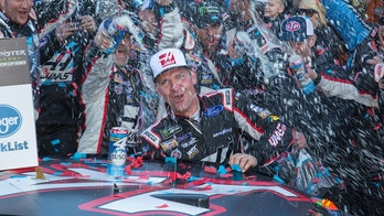 Clint Bowyer, center, celebrates with his crew after winning a NASCAR Cup Series auto race at Martinsville Speedway in Martinsville, Va., Monday, March 26, 2018. (AP Photo/Matt Bell)