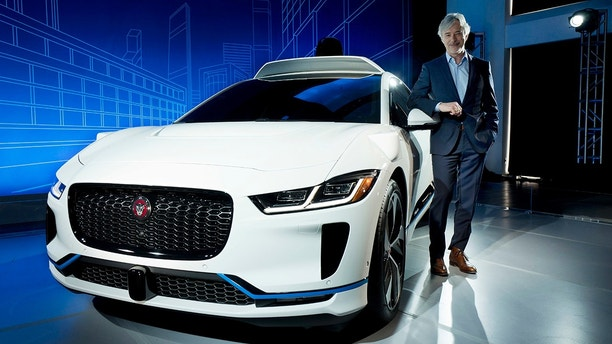 John Krafcik, the CEO of Waymo, stands with the Jaguar I-Pace vehicle, Tuesday, March 27, 2018, in New York. Self-driving car pioneer Waymo will buy up to 20,000 of the electric vehicles from Jaguar Land Rover to help realize its vision for a robotic ride-hailing service. (AP Photo/Mark Lennihan)