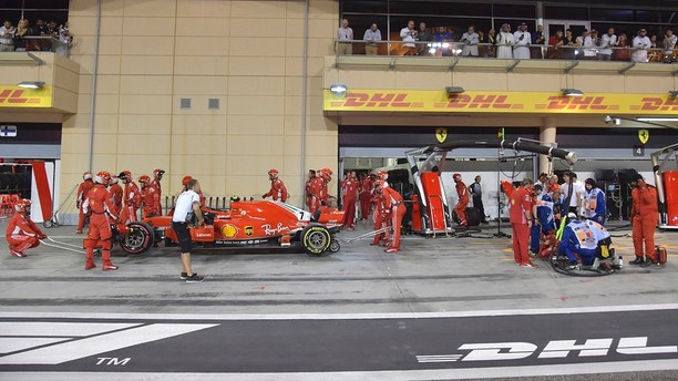 Ferrari mechanic Francesco lies on the ground right after being bitted by Ferrari driver Kimi Raikkonen during a pit stop the Bahrain Formula One Grand Prix at the Formula One Bahrain International Circuit in Sakhir Bahrain Sunday
