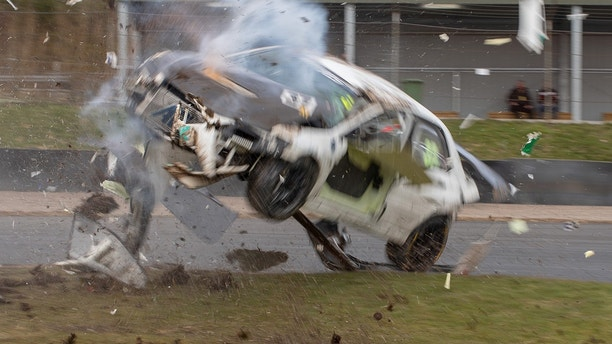 The Mitsubishi Evo crash at Knockhill Racing Circuit, near Dunfermline, Scotland. See Masons copy MNCRASH: These pictures capture the moment a racing car was sent spinning metres into the air before rolling along the ground with debris flying - and the driver walking away without a scratch. Kenneth McKell was caught up in the almost deadly crash after the front brakes on his white Mitsubishi Evo reportedly failed, causing the ones at the rear to lock up. The vehicle started to spin as it approached a corner of the track before hitting the tire wall and launching into the air, barely clearing the top of a marshall's hut.