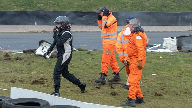Driver Kenneth McKell leaves the wreck without a scratch at Knockhill Racing Circuit, near Dunfermline, Scotland. See Masons copy MNCRASH: These pictures capture the moment a racing car was sent spinning metres into the air before rolling along the ground with debris flying - and the driver walking away without a scratch. Kenneth McKell was caught up in the almost deadly crash after the front brakes on his white Mitsubishi Evo reportedly failed, causing the ones at the rear to lock up. The vehicle started to spin as it approached a corner of the track before hitting the tire wall and launching into the air, barely clearing the top of a marshall's hut.