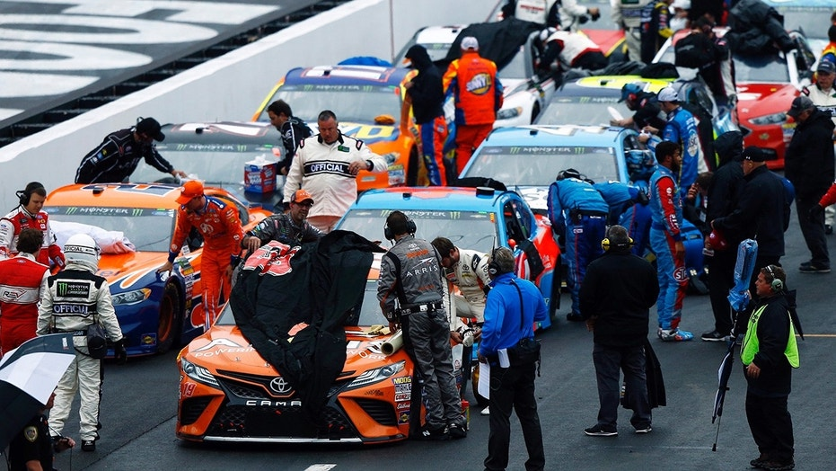 Crews cover the cars as rain falls during a NASCAR Cup Series auto race, Sunday, April 15, 2018, in Bristol, Tenn. (AP Photo/Wade Payne)
