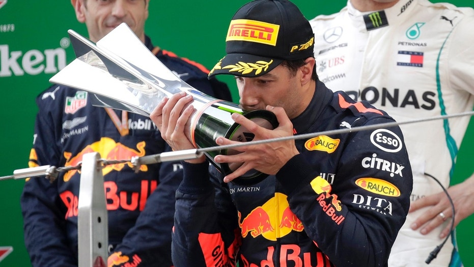 Red Bull driver Daniel Ricciardo of Australia kisses his trophy as he celebrates after winning the Chinese Formula One Grand Prix at the Shanghai International Circuit in Shanghai, Sunday, April 15, 2018.