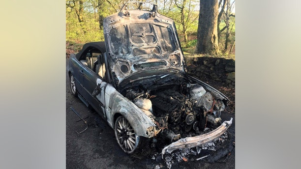 """Raymond and Barbara Massey had a lucky escape after his convertible sports car burst into flames as he drove his wife to their anniversary dinner near Bolton, Greater Manchester. See Ross Parry story RPYFIRE;A motorist had a lucky escape after his convertible sports car burst into flames as he drove his wife to their ANNIVERSARY dinner.  Raymond Massey, 77, managed to pull his wife, Barbara, who uses a wheelchair after suffering a stroke 18-months-ago, to safety after being alerted to the fire by a passerby. Stunned witnesses described an """"enormous explosion like a bomb had gone off"""" after noticing flames on the road and smoke coming from the bonnet of the car.  The couple miraculously managed to avoid serious injury after the engine of the blue BMW 3 Series set on fire, which they blame on hitting two POTHOLES.  Crews rushed to the scene and spent an hour tackling the fire in Bolton, Greater Mancs., at around 5.30pm on Sunday."""