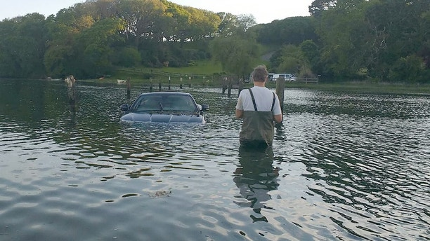 """This picture shows the moment an expensive Jaguar was consumed by water - after the owner left the car parked on a tidal road. See SWNS story SWJAG; The black Jaguar XK, which cost around £60,000 when new, can be seen with the boot open and water nearly to the top of the windows. Chris and Gill Freeborn were passing in their boat when they spotted the unfortunate situation, and quickly took some snaps. Gill said the sight made her """"howl with laughter"""", and Chris said the Jaguar was """"clearly not a happy pussy cat"""". The car, worth around £10,000 on the current market, has now been removed from Aveton Gifford tidal road in Kingsbridge, Devon."""