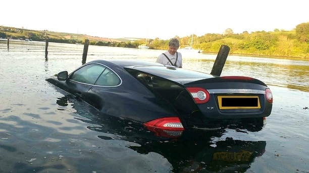 "This picture shows the moment an expensive Jaguar was consumed by water - after the owner left the car parked on a tidal road. See SWNS story SWJAG; The black Jaguar XK, which cost around £60,000 when new, can be seen with the boot open and water nearly to the top of the windows. Chris and Gill Freeborn were passing in their boat when they spotted the unfortunate situation, and quickly took some snaps. Gill said the sight made her ""howl with laughter"", and Chris said the Jaguar was ""clearly not a happy pussy cat"". The car, worth around £10,000 on the current market, has now been removed from Aveton Gifford tidal road in Kingsbridge, Devon."