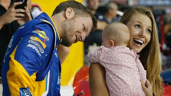 Dale Earnhardt Jr., left, looks at his daughter, Isla, and his wife Amy on pit row prior to an Xfinity Series NASCAR auto race at Richmond Raceway in Richmond, Va., Friday, Sept. 21, 2018. (AP Photo/Steve Helber)
