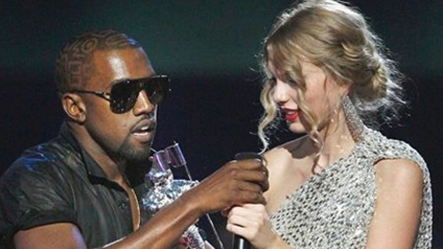 "Singer Kanye West takes the microphone from singer Taylor Swift as she accepts the ""Best Female Video"" award during the MTV Video Music Awards on Sunday, Sept. 13, 2009 in New York.  (AP Photo/Jason DeCrow)"