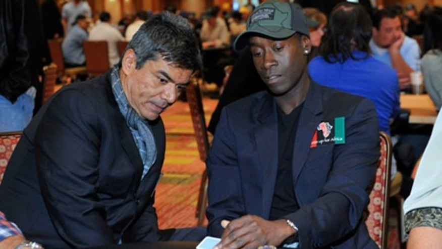 Don Cheadle showing George Lopez his hand at the second annual Ante Up For Africa Tournament .
