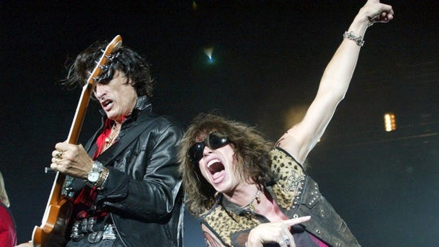 Aerosmith's lead singer Steven Tyler, right, belts out the tune beside guitarist Joe Perry during their Tokyo Dome concert in Tokyo.