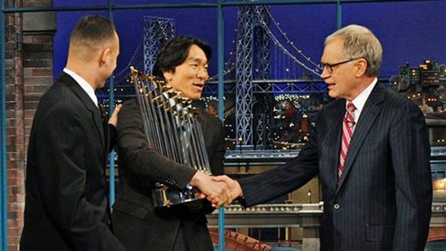 "Nov. 5: In this photo released by CBS, host David Letterman, right, shakes hands with New York Yankees' Hideki Matsui, center, as teammate Derek Jeter looks on during an appearance on the ""Late Show with David Letterman."""