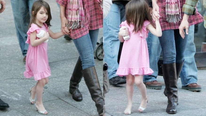 Suri Cruise is seen in high heels with her parents in October