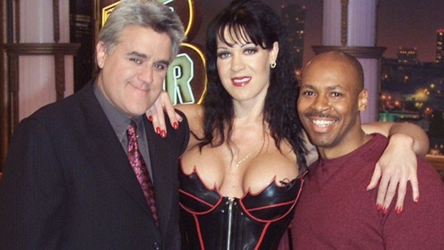 "World Wrestling Federation wrestler Chyna poses with talk show host Jay Leno and band leader Kevin Eubanks on the set of ""The Tonight Show."" (Reuters)"