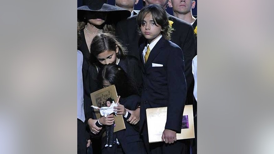 Paris Jackson holds Blanket, while Prince Jackson looks on during their father's memorial service last year.