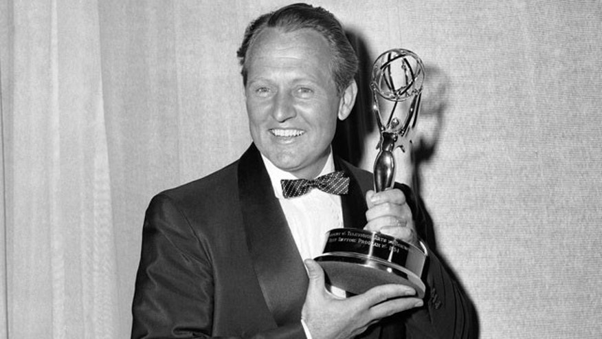 This March 7, 1955 file photo shows Art Linkletter posing with the Emmy awarded to him by the Television Academy for the best daytime program, in Los Angeles.