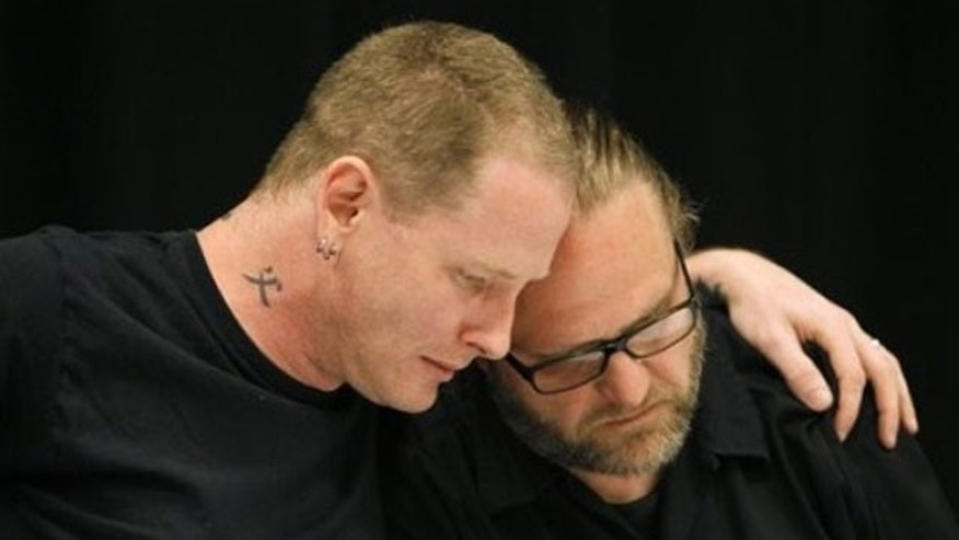 May 25: Slipknot lead singer Corey Taylor, left, reacts with band member Shawn Crahan after speaking about the death of bassist Paul Gray during a news conference in Des Moines, Iowa.