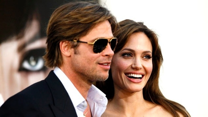 "Angelina Jolie and actor Brad Pitt pose at the premiere of ""Salt"" in Hollywood, California July 19, 2010. (Reuters)"