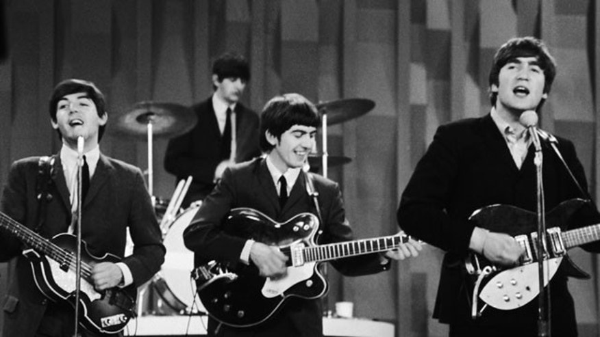 "In this Feb. 9, 1964 file photo, The Beatles  perform on the CBS ""Ed Sullivan Show"" in New York. Ringo Starr plays drums, rear, and playing guitars from left are Paul McCartney, George Harrison and John Lennon."