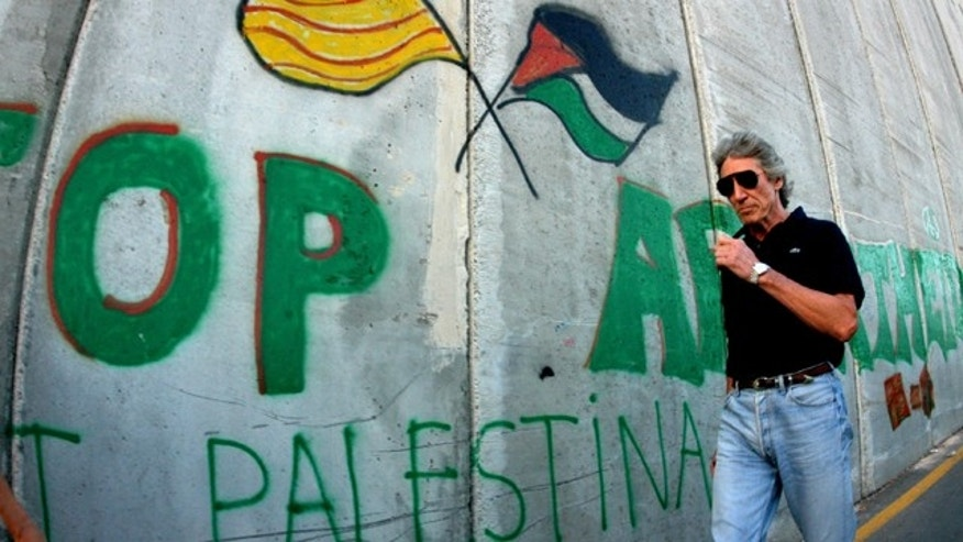 Roger Waters of Pink Floyd walks along the Israeli barrier in the West Bank city of Bethlehem June 21, 2006. (Reuters)