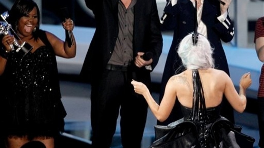 "From left, Amber Riley, Cory Monteith, and Jane Lynch, of the cast of Glee present Lady Gaga with the award for best pop video for ""Bad Romance"" at the MTV Video Music Awards on Sunday, Sept. 12, 2010 in Los Angeles. (AP Photo/Matt Sayles)"