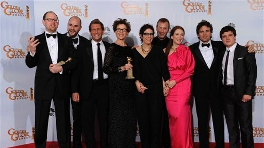 "The cast and crew of ""The Kids Are All Right,"" pose with the award they won for Best Motion Picture - Comedy Or Musical at the Golden Globe Awards Sunday, Jan. 16, 2011, in Beverly Hills, Calif. (AP Photo/Matt J. Terrill)"